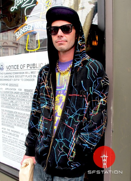 Photo by Lily Ko<br /> <br /> In This Scene:  Shane Jordan looking hip-hop skater chic in the Haight. He's wearing a DC hoodie with a subway map print and a t-shirt from Major Lazer Recrods. Jordan's gold chain was just purchased at Piedmont Boutique--go big or go home, homie!