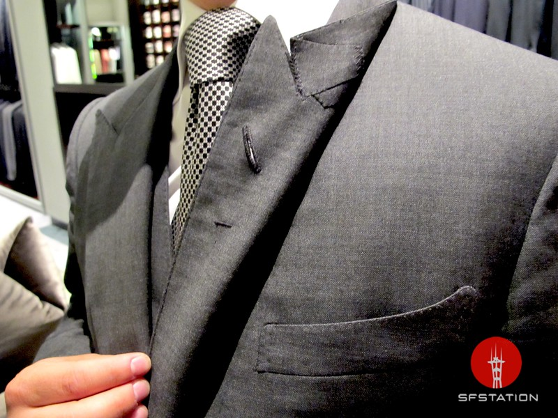 Photo by Lily Ko<br /> <br /> In This Scene:  A closer look at the details in this Tom Ford Windsor-cut suit. This suit features the iconic Tom Ford peak lapels and pick stitching. All Tom Ford suits are hand sewn--the boutonniere hole alone takes 10 minutes to sew. The tiny horizontal stitch under the boutonniere hole is a tribute to old-school tailoring. Suits used to feature this to hold the small water vase for your flowers.