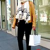 Photo by Lily Ko<br /> <br /> In This Scene:  Mali Riv, a physician, caught while shopping around Union Square. Everything she is wearing--right down to her flip flops--is Club Monaco, except for her jacket. The tan leather jacket was purchased in Canada. I just really like the color combination here with the speck of metallic in her shoes, cream scarf, tan jacket and bold, square sunglasses.