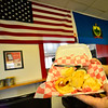 Eddie Cagliano, owner of Fast Eddies, on Putney Road, in Brattleboro, holds up a freshly made deep-fried haddock on Friday, Feb. 28, 2020.