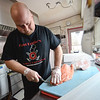 KRISTOPHER RADDER — BRATTLEBORO REFORMER<br /> Jason Chalke, the chef at Fast Eddies, cuts the skin of a fresh order of salmon that will be used on Friday, Feb. 28, 2020.