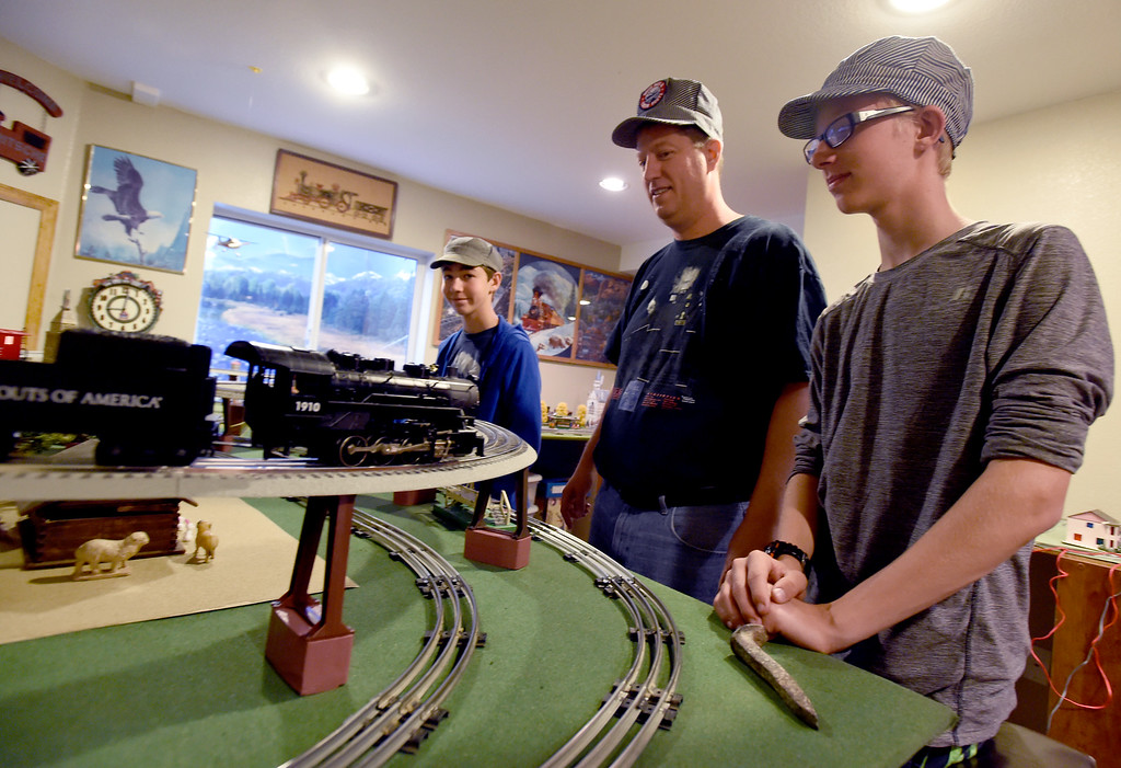 """. Dan Fritsche, center, and his sons, Luke, left, and Timothy, talk about their  train set, one of their primary train sets. Dan Fritsche and his sons, Timothy and Luke, continue to build on \""""Fritscheville\"""" -- the tiny mobile train town his grandfather began building in 1923, with every generation in the family adding onto it. For more photos and a video, go to www.dailycamera.com.  Cliff Grassmick  Staff Photographer June 16, 2017"""