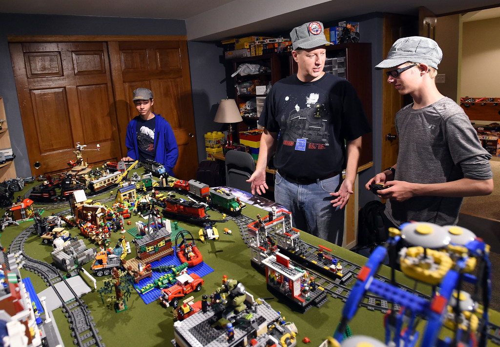 """. Dan Fritsche, center, and his sons, Luke, left, and Timothy, talk about their Lego train set, one of their primary train sets.  Dan Fritsche and his sons, Timothy and Luke, continue to build on \""""Fritscheville\"""" -- the tiny mobile train town his grandfather began building in 1923, with every generation in the family adding onto it. For more photos and a video, go to www.dailycamera.com.  Cliff Grassmick  Staff Photographer June 16, 2017"""