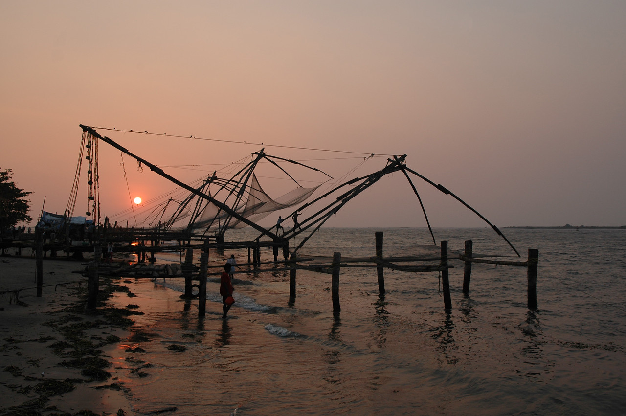 A Chinese fishing net is dipped into the water as the sun sets behind it in Fort Cochin