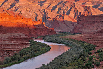 San Juan Reflections. Sunset light reflecting off the red rock of the Raplee Anticline near Mexican Hat, Utah gives a glow to the San Juan River.