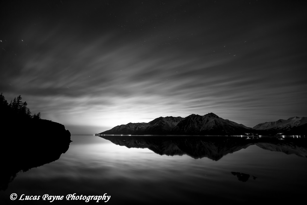 The Chugach Mountains and glow of the city lights of Anchorage reflected in the calm waters of Turnagain Arm<br /> <br /> April 13, 2012