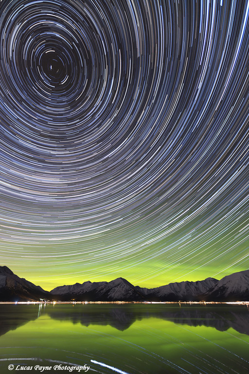 Star trails circle above the Chugach Mountains with the green glow of the Aurora Borealis reflecting in Turnagain Arm, Southcentral Alaska<br /> <br /> March 16, 2013