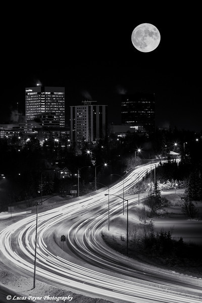 A full moon hovers over the skyline of downtown Anchorage and rush hour traffic on Minnesota Drive, Southcentral Alaska.<br /> <br /> December 16, 2013