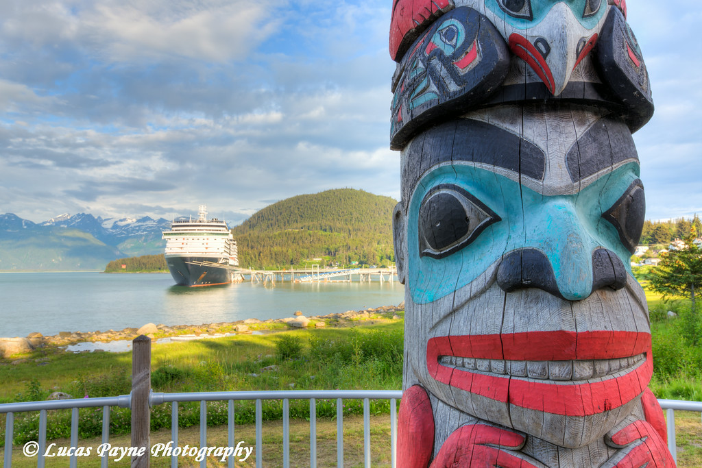 Totem Pole and the Holland America Cruise Ship Oosterdam docked at the Port of Haines, Southeast Alaska.<br /> <br /> July 02, 2014