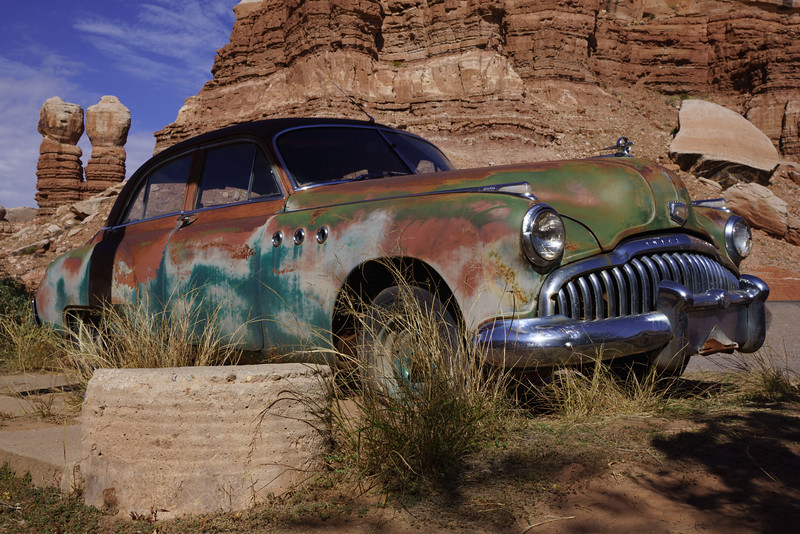 Twin Rocks in the background, this old Buick is  a fixture at  the Cow Canyon Gallery