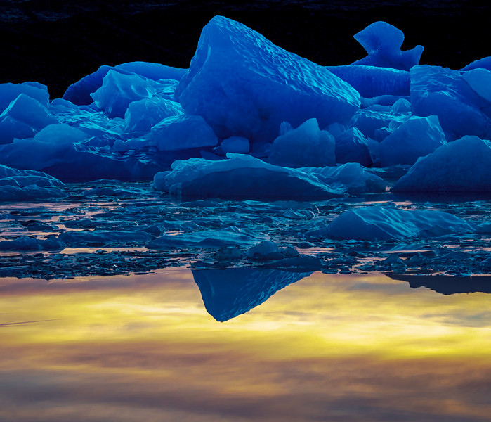 Reflection of an ice block floating down a river at sunset...Iceland