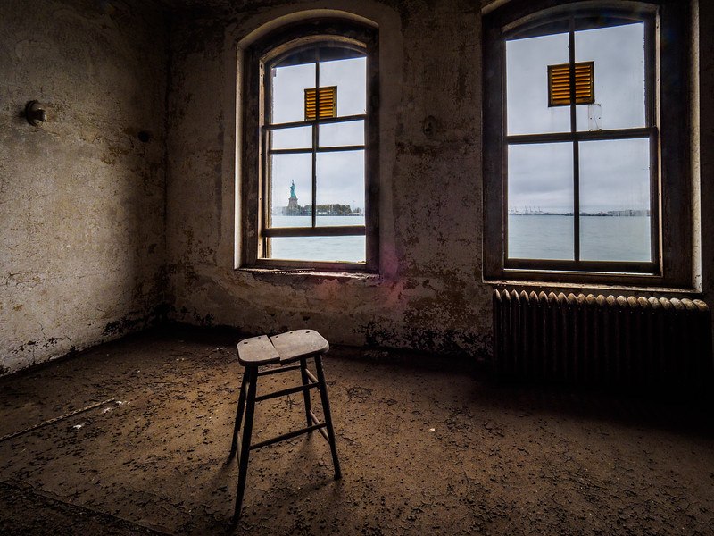 Golden interior lighting, with Statue of Liberty viewed through window in one of the rooms at the abandoned medical compound on Ellis Island...New York