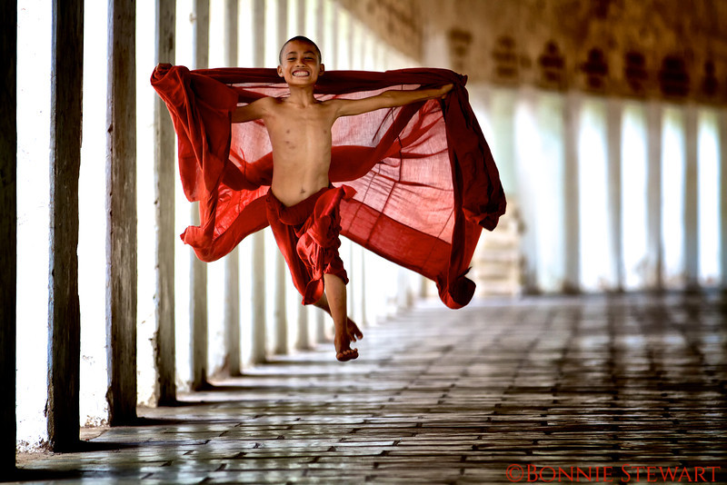 """Flying Monk!  A young monk runs down the eastern corridor of the Shwezigon Pagoda in Bagan and becomes airborne in his excitement of life  This image was published by National Geographic in the book, """"Stunning Photographs"""" by Annie Griffiths, October 2014, pp. 18-19"""