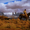 Patagonian Gaucho <br /> Chilean Gaucho Christian Sanchez rides off to retrieve a sheep for dinner on a remote ranch in Patagonia. Torres del Paine is in the background.