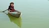 Elderly man paddling on the Mekong River