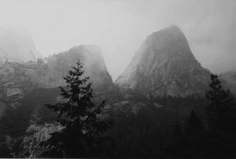 Yosemite in October fog.<br /> Fog pictures are often disappointing, but I like this one as I think it conveys a sense of awe and mystery that is so well suited to the transcendent and grandiose place that Yosemite is.<br /> <br /> (B&W, scanned)