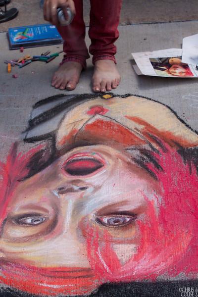 Spraying a completed work - Sidewalk art in chalk
