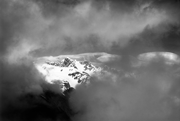 The Southern Alps peaking through the clouds.  South Island, New Zealand