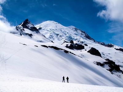 Climbers dwarfed by Mt. Rainier and Little Tahoma, Mt. Rainier NP, WA