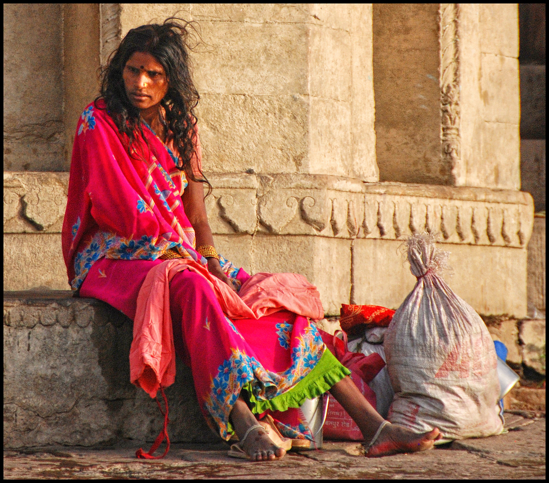 Woman resting after washing clothes in the Ganges.
