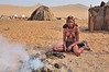 Himba girl tending the cooking fire fuelled with dried cattle manure