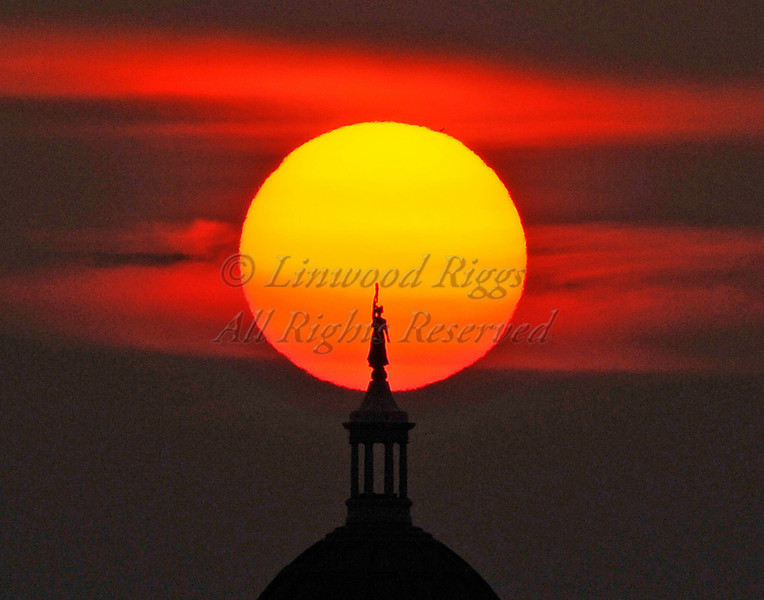 The Lady of Wisdom statue atop the Maine State Capitol in Augusta is silhouetted against the setting sun. (And no, it's not a photo montage!)