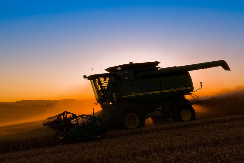 A combine harvests wheat in the Palouse region of Washington at sunset