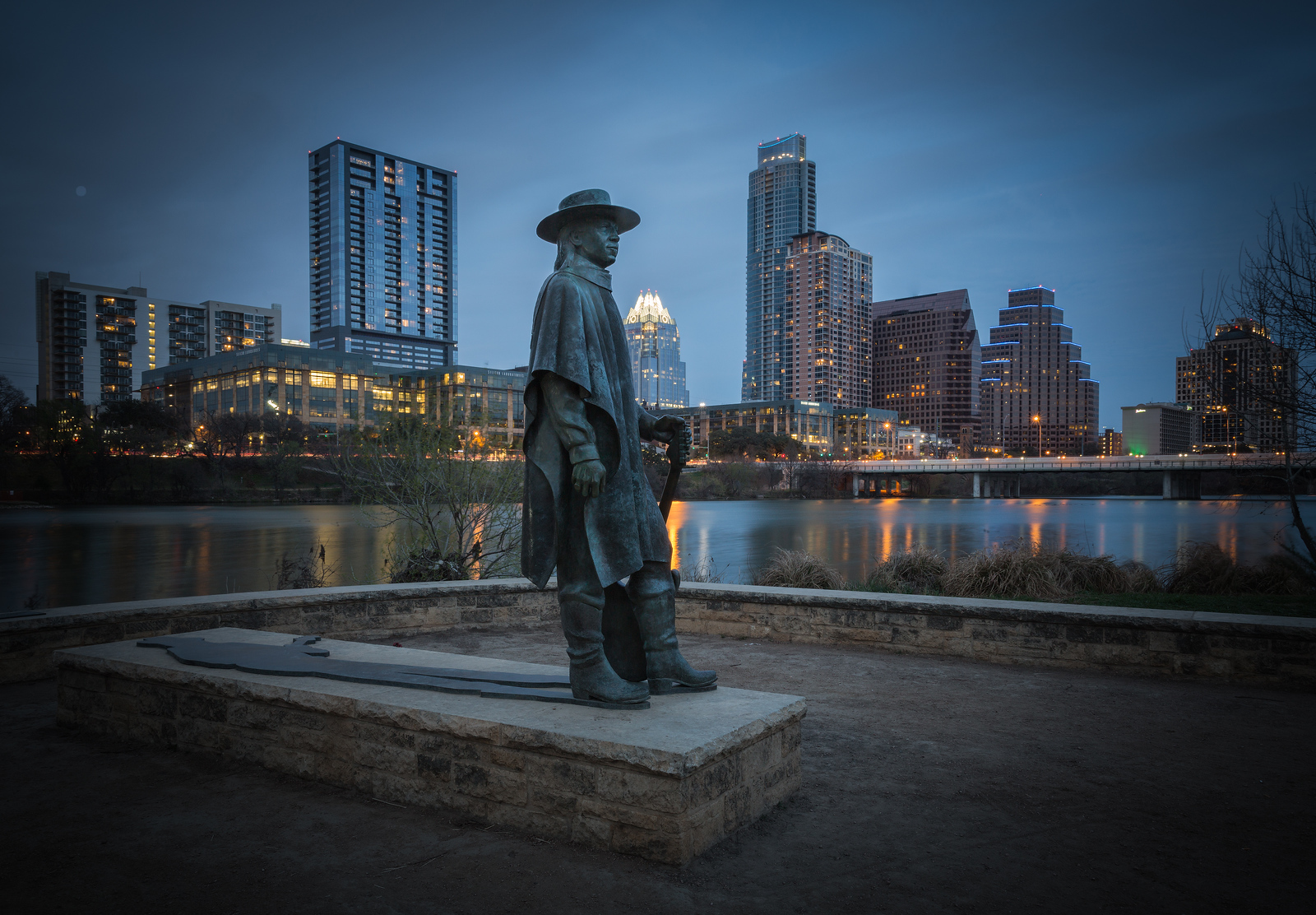 Stevie Ray Vaughn statue on Lady Bird Lake w/ ATX skyline