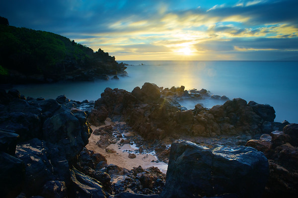 Treacherous rocks surround a small cove where angels play as the remaining golden light fades into the horizon.