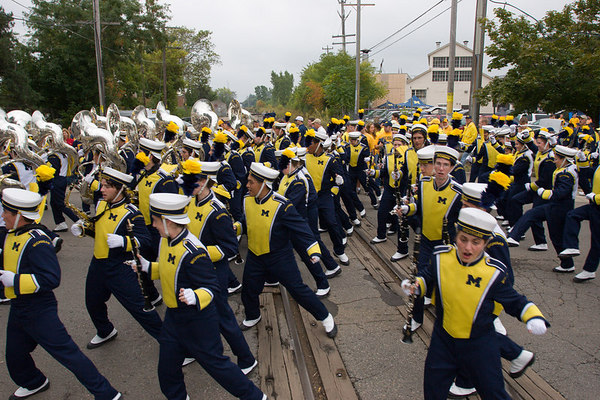 the michigan marching band dancing across the railroad tracks on the way home from the stadium.