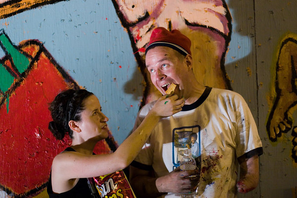 during a break from the mural they were painting together, dana ellyn feeds sun chips to matt sesow.