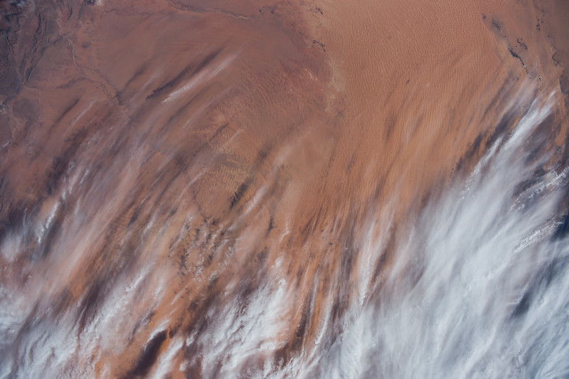 Reid Wiseman @astro_reid  Oct 30 Red sands in #Africa brushed by clouds – #EarthArt