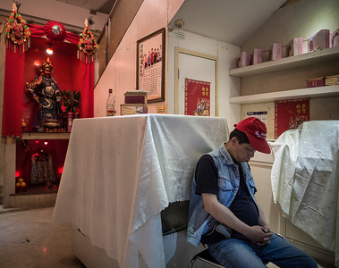 A man dozes at night in Wanchai, Hong Kong.