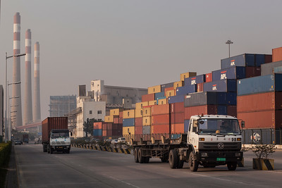 Truckers drive past stacks of transport containers at Chiwan Container Terminals, Port of Shekou in Shenzhen, Guangdong Province, China on Friday, Jan. 7, 2011. Photographer: Forbes Conrad/Bloomberg News