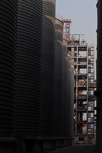 A worker walks down a flight of stairs between silos at the Port of Shekou in Shenzhen, Guangdong Province, China on Friday, Jan. 7, 2011. Photographer: Forbes Conrad/Bloomberg News