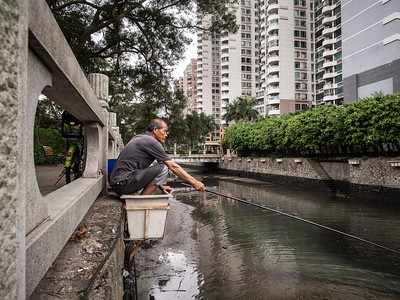 A man fishes a canal from his perch in an empty flower planter box in Zhuhai, China.