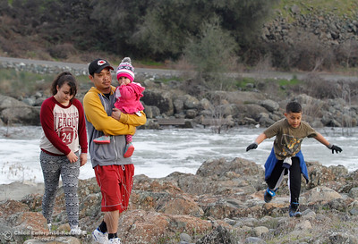 Kao Saechao (center) brings his children May, 12, Amyah 15 months and Daymien, 9, to the Feather River to observe the excess water flowing January 31, 2017 in Oroville, California. (Emily Bertolino -- Enterprise-Record)