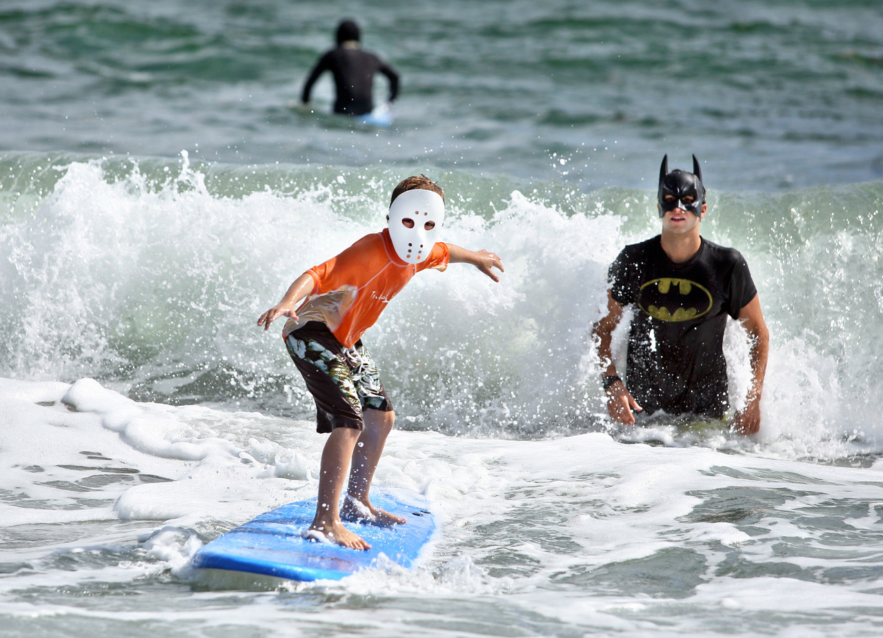 """102613 - DELRAY BEACH - Ryan Lutwin, 9, catches a wave with the help of batman, aka Eric Dernick, who runs Waves Surf Academy. Ryan, who lives in Davie, was visiting his grandmother Audrey Dunn who lives in Boynton Beach.  On Saturday morning from 11 a.m. to 2 p.m., kids were treated to a free surf lesson from Waves Surf Academy.The only catch, they have to wear a costume to participate in the """"Monster Thrash Surf-Off.""""  Photo by Tim Stepien"""