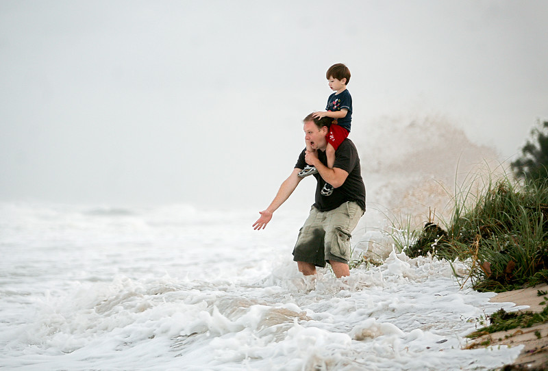 102712 - DELRAY BEACH -  Jeff Beck and his son Hayden were caught off guard when a wave crashed into them on the beach in Ocean Ridge. Jeff and his family were visiting South Florida from Snellville Georgia.  Photo by Tim Stepien