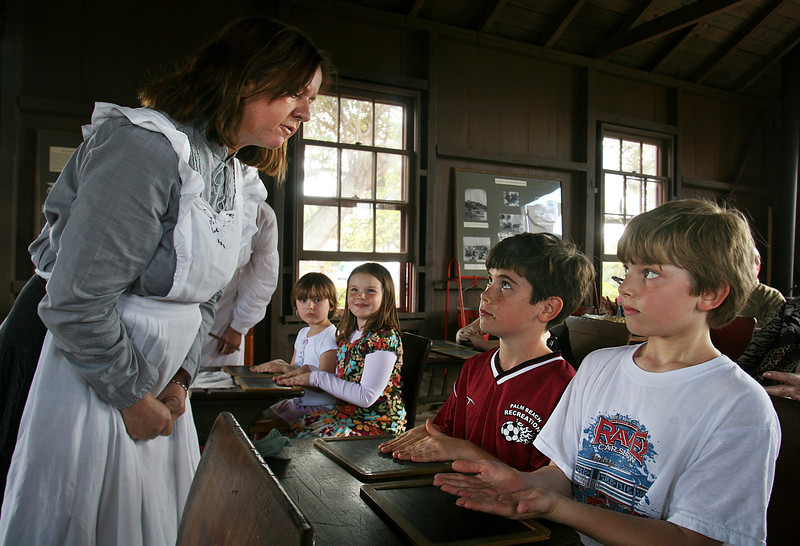 011511 - PALM BEACH - Centennial Pioneer Day held at Phipps Ocean Park, 2185 S. Ocean Blvd., Palm Beach. A typical 1886 school day was reenacted inside of the Little Red Schoolhouse that was built in 1886. At left, mock teacher Michele Thompson of The Preservation Society examines the nail length and hand cleanliness of students Eddie Force, 9, WPB (maroon shirt) and Isaac Jones, 9, Palm Beach.  Nail biting was said to promote childhood diseases. Photo by Tim Stepien