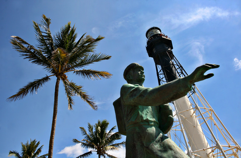 030913 - HILLSBORO - Memorial to barefoot mailman at Hillsboro Lighthouse. On Saturday, March 9th, Hillsboro Inlet Lighthouse celebrated its 106th Anniversary. The lighthouseis located on the north side of Hillsboro Inlet, midway between Fort Lauderdale and Boca Raton, in Hillsboro Beach, Florida. The light marks the northern limit of the Florida Reef, an underwater coral formation on the lower east coast of the state. The octagonal iron pyramidal tower was built at Russel Wheel & Foundry Co in Detroit, Michigan, moved to the Hillsboro Inlet Light Station in 1906, and lit on March 7, 1907. While visiting the lighthouse, you learn the story of the barefoot mailmen, honored with a memorial statue. The mailmen walked more  than 40 miles of sandy shore each week to deliver mail between Palm Beach and Miami 1885 to 1892. One mailman died at the Hillsboro Inlet, presumably killed by an alligator. Photo by Tim Stepien