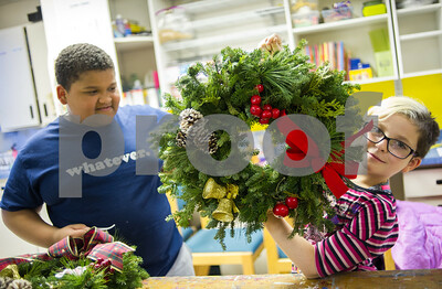 Robert Layman / Staff Photo Coran Rowdy looks at Auriella Hawkins (QP) as she holds her wreath up at the Rutland County Boys & Girls Club Wednesday night, Dec. 7, 2017. Members of the Rutland Garden Club brought the children wreaths and craft supplies, which enabled them to craft 17 wreaths to decorate their homes with.
