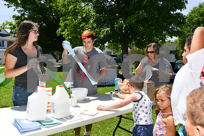 Michael's employees Sam May-Amerio, center, and Amelia Ashley-Selleck, left, make slime for a patient line of children during the Rutland Summer Meals Kick Off in Main Street Park in Rutland Tuesday afternoon. (Robert Layman / Staff Photo)