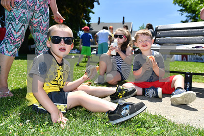 Jacob Hilder, left, 3, of Rutland, eats with his sister, Bryanna, 5, and his cousin at the Rutland Summer Meals Kick Off in Main Street Park in Rutland Tuesday afternoon. (Robert Layman / Staff Photo)