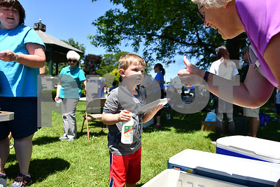 Lincoln Brown, 3, of Rutland gets a pint of milk at the Rutland Summer Meals Kick Off in Main Street Park in Rutland Tuesday afternoon. (Robert Layman / Staff Photo)