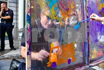 Fire fighter Adam Macintosh paitns a fire truck and sticks a Rutland City Fire Department sticker on his artistic creation. (Robert Layman / Staff Photo)