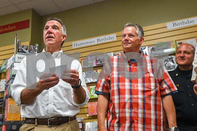 Governor Phil Scott calls out a lucky winner to the $10 gift certificate drawling at Phoenix Bookstore Friady night. (Robert Layman / Staff Photo