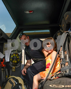 Lyla Doll, 4, of Maryland, sits with Adam Macintosh of the Rutland City Fire Department in one of the transportation units during the Friday Night Live celebration. (Robert Layman / Staff Photo)