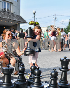 Merin Blair, 5, of Rutland lifts up a chess piece as her mother Caitlin watches during a game. (Robert Layman / Staff Photo)