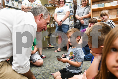"Governor Phil Scott hands out a $10 gift certificate prize to Avery Barnes, center, at Phoenix Bookstore Friday night. Bookstore manager Will Notte said ""Barnes deserved it. He was here thirty minutes before everyone."" Members of the Rutland City Police Department read tales to the children during the Friday Night Live events. (Robert Layman / Staff Photo"